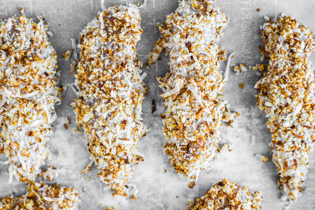 Chicken tenders coated in toasted coconut and crumbs.