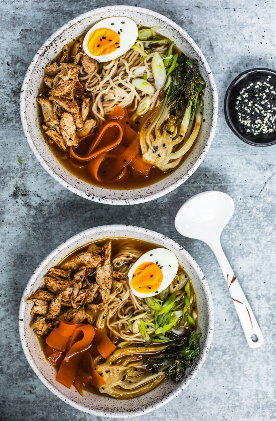 Two bowls of Five Spice chicken Ramen side by side, both topped with soft-boiled eggs, seared bok choy, and ribboned carrots.