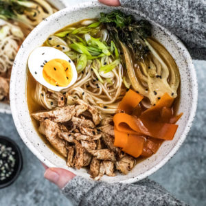 Hands holding up five spice chicken Ramen bowl topped with an egg and vegetables.