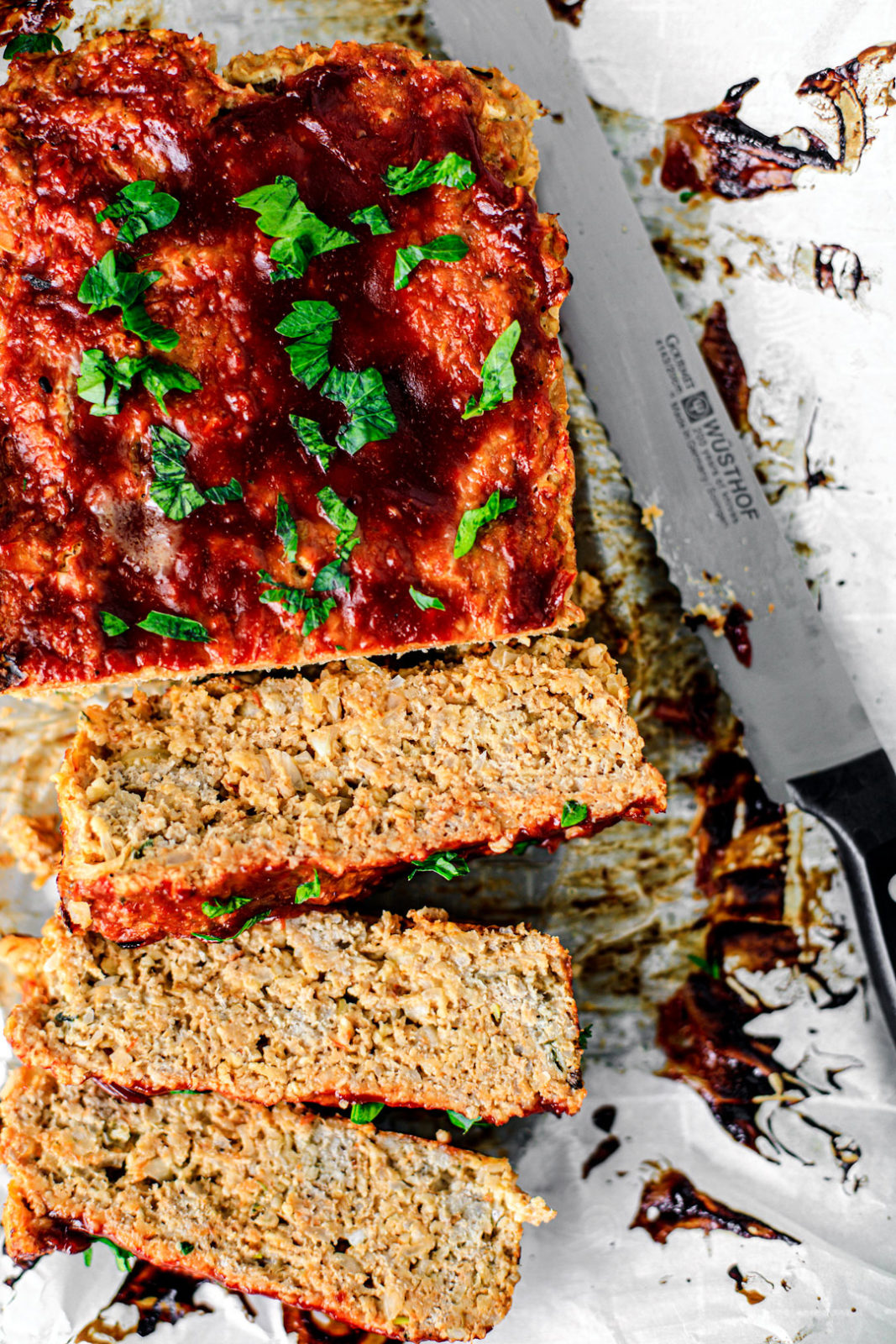 Meatloaf partially sliced over parchment paper, garnished with bright green parsley.