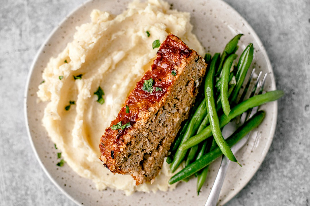 Slice of ground turkey meatloaf on a plate with mashed potatoes and green beans.