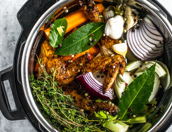Overhead view of Instant Pot filled with water, colorful vegetable scraps, and roasted chicken scraps.