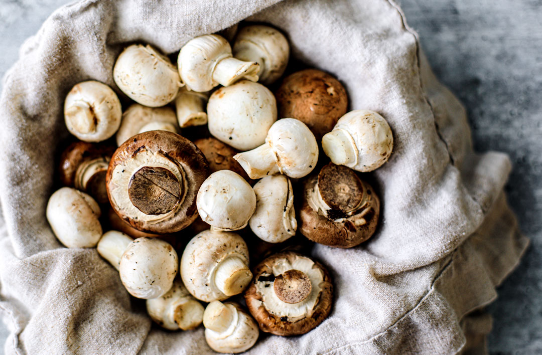 Bowl full of cremini and button mushrooms.