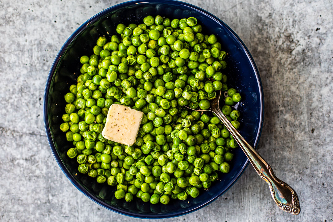 Bowl full of bright green peas with a pat of melting butter on top.