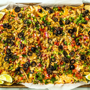 Sheet pan full of baked cheesy nachos covered in veggies and mackerel.
