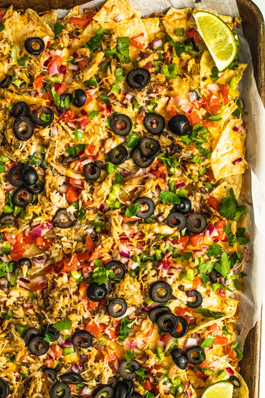 Close up vertical shot of sheet pan full of baked cheesy nachos covered in veggies and mackerel.