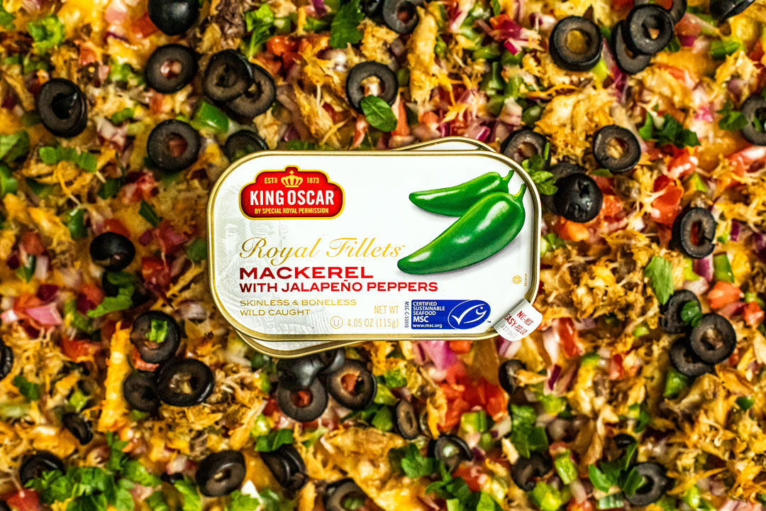 Tins of King Oscar Mackerel with Jalapeno Peppers sitting atop sheet pan nacho platter.