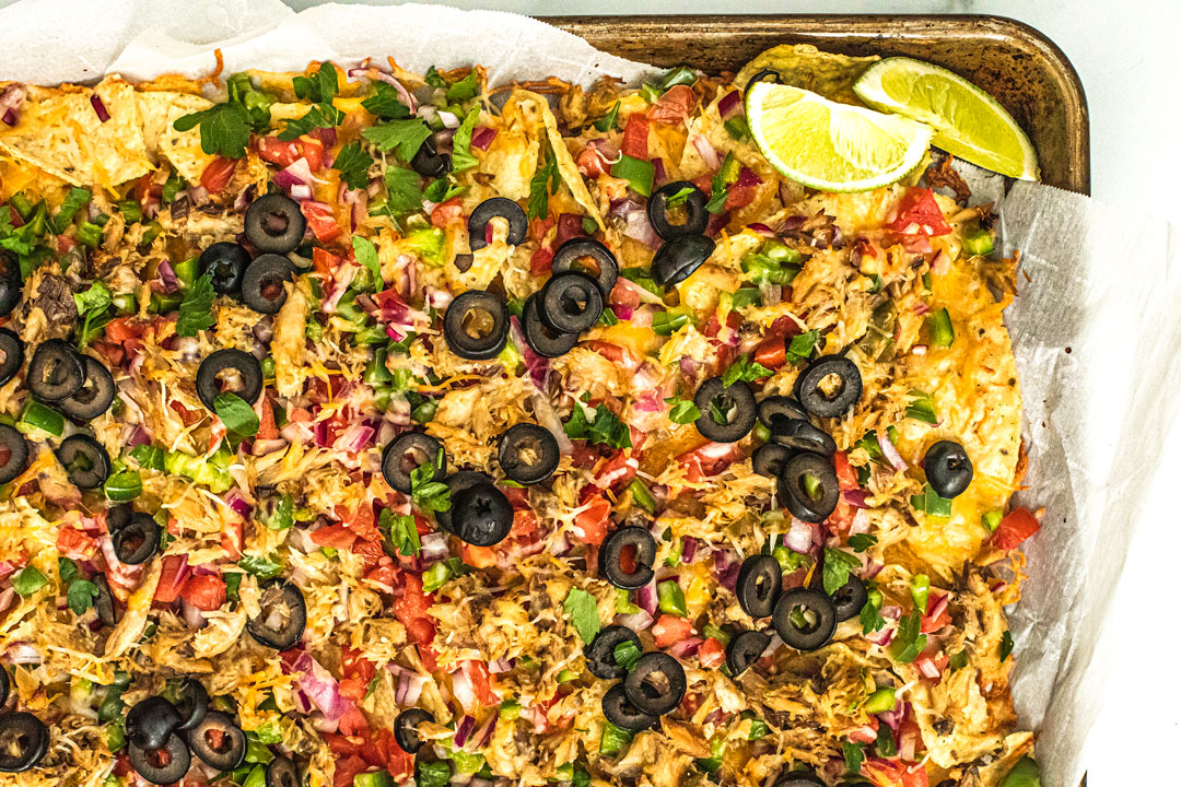 Sheet pan full of baked cheesy nachos covered in veggies and mackerel.