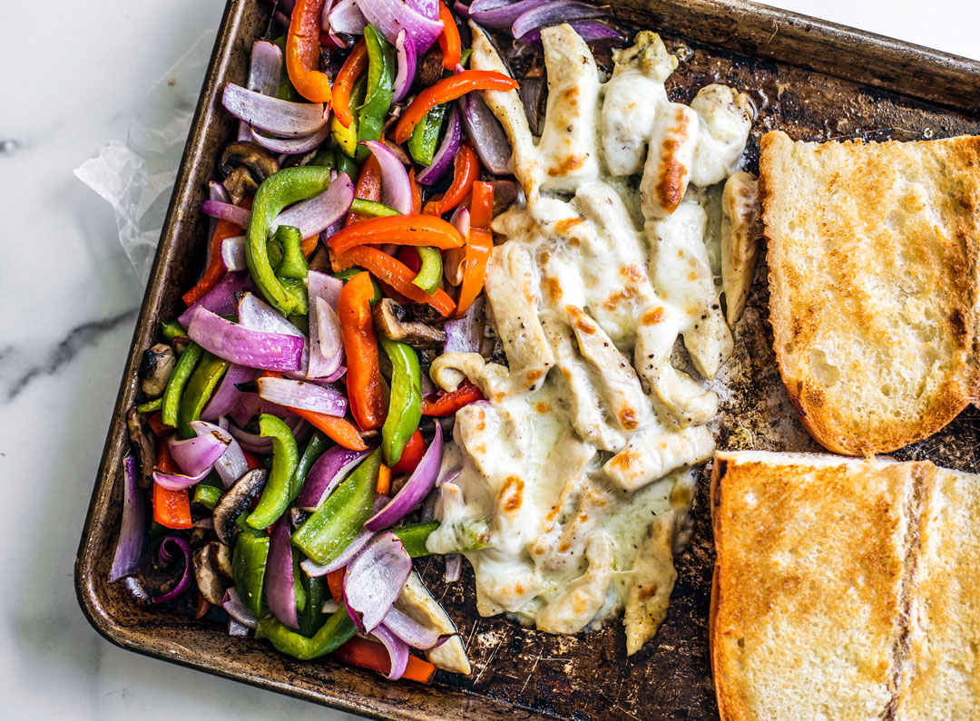 Sheet pan full of onions, peppers, mushrooms, cheesy chicken, and toasted bread.