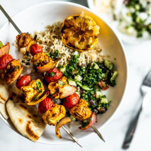 Plate of rice, tabbouleh, and pitas with grilled Moroccan chicken skewers on top.