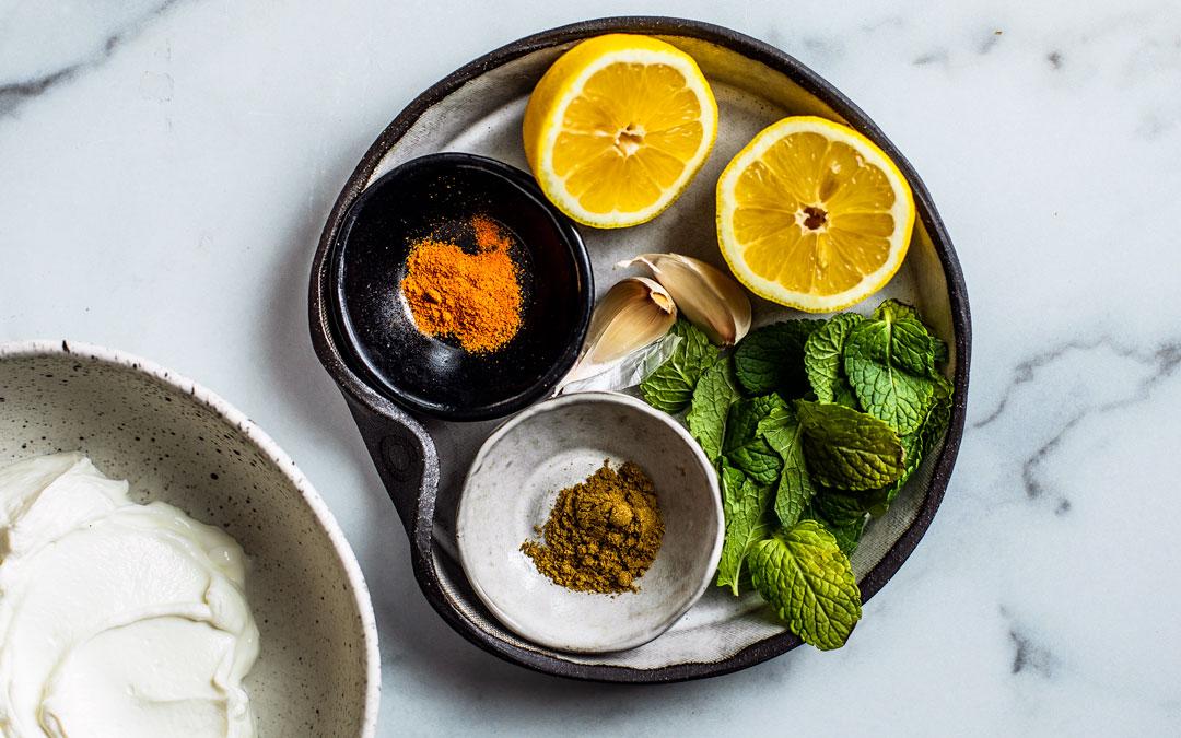 plate full of ingredients for mint Greek yogurt dip: mint leaves, lemons, spices, and garlic cloves.