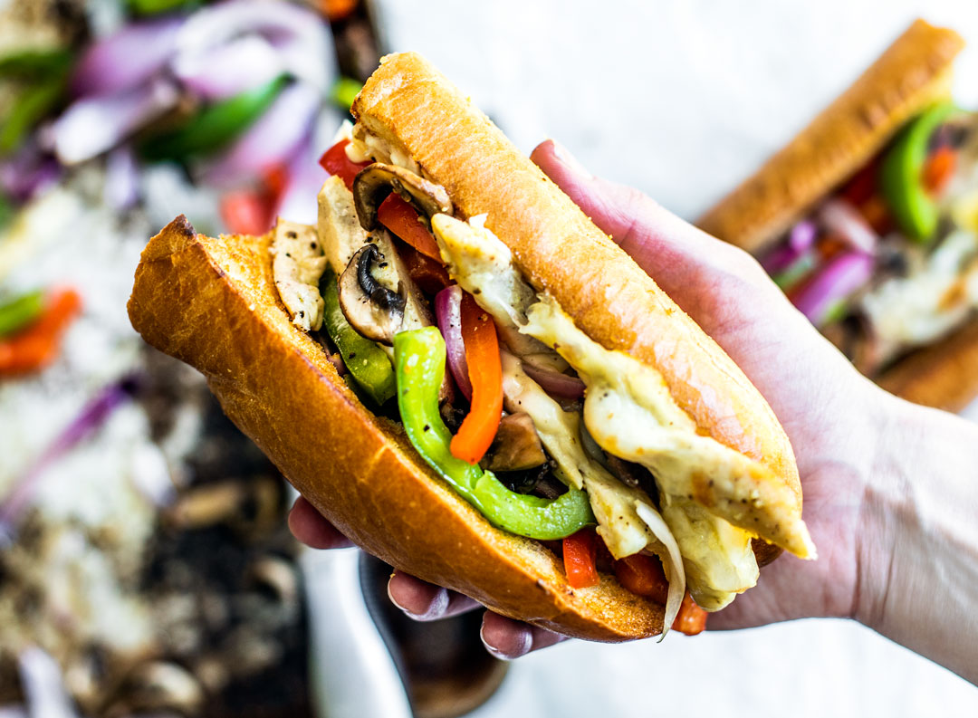 Hand holding out a Chicken Philly Cheesesteak sandwich.