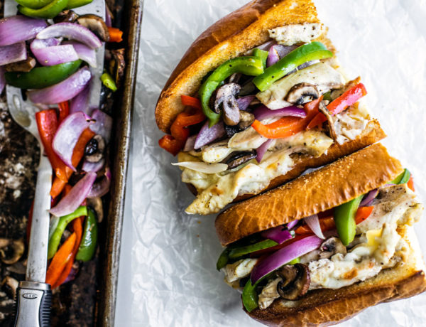 Chicken Philly Sandwich next to a sheet pan full of peppers, onions, and mushrooms.