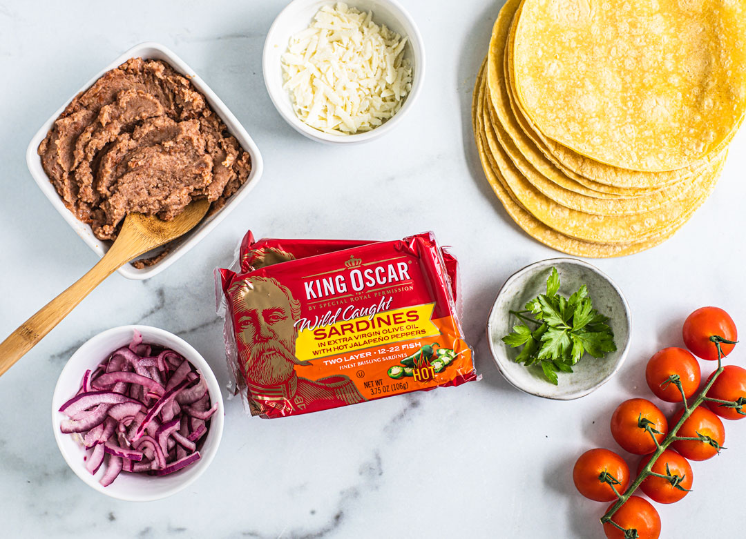 A tablescape of ingredients: refried beans, onions, tomatoes, cheese, parsley, corn tortillas, and packages of King Oscar sardines.