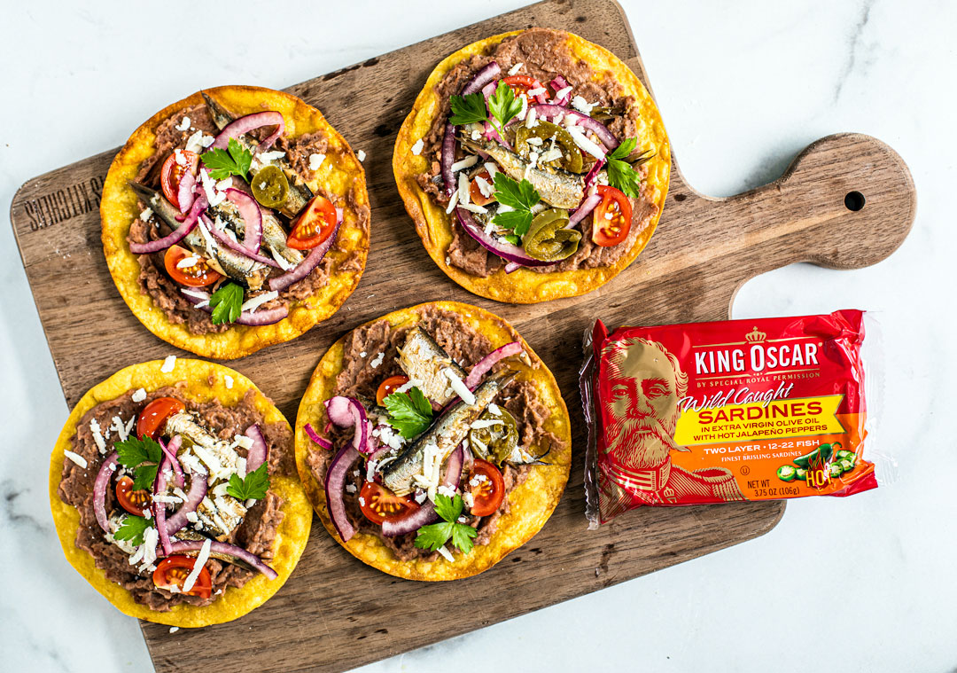 Wooden serving board with spicy tostadas and King Oscar sardine tin.