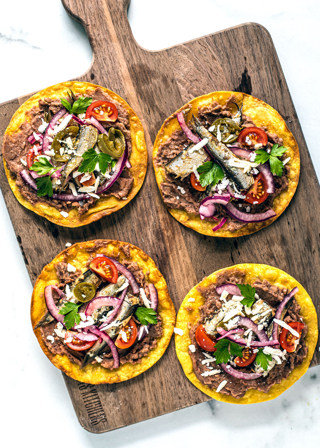 Wooden serving board with spicy tostadas on top.