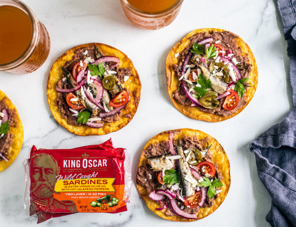 Spicy tostadas laid out around pints of beer and cans of King Oscar sardines.