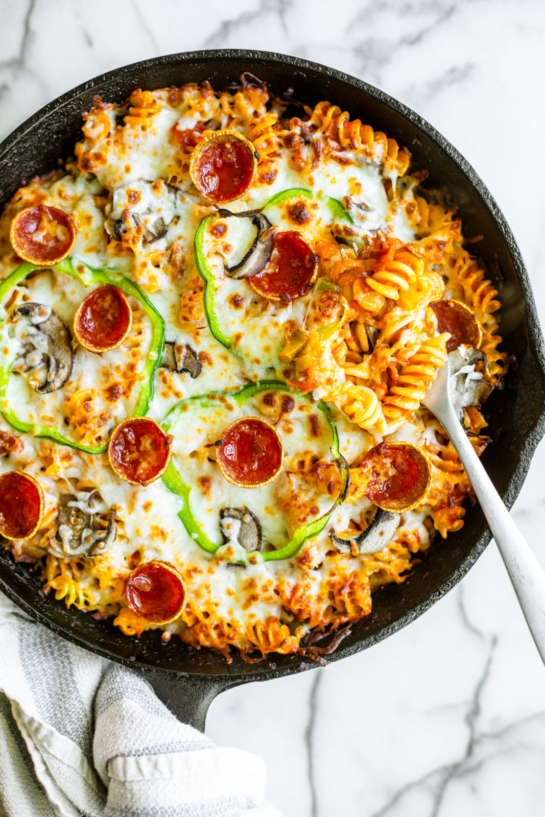 Skillet of cheesy pizza pasta with a fork pressed into rotini.
