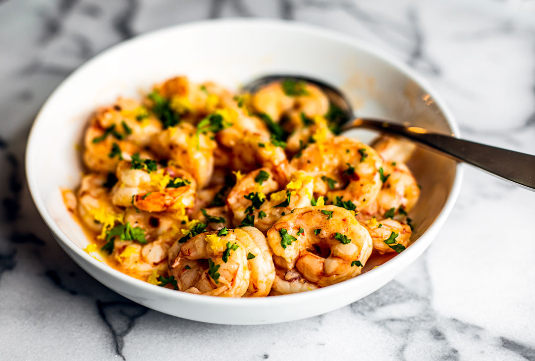 Side shot of white serving bowl full of butter shrimp garnished with fresh parsley.