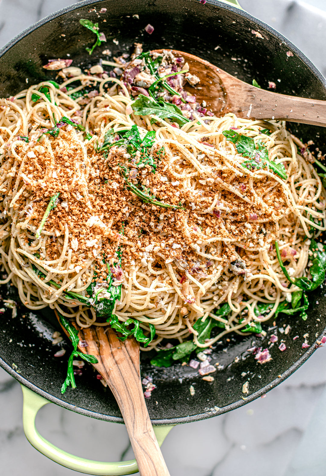 Pasta stired up in a pan with arugula and toasted breadcrumbs.