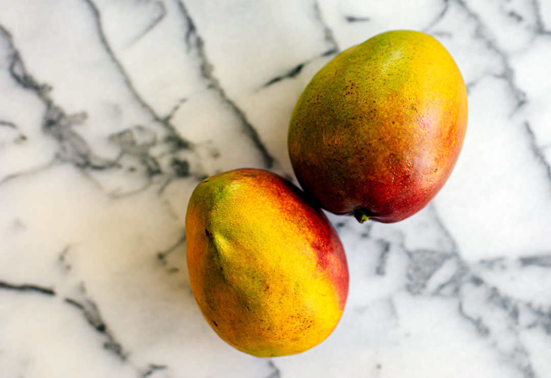 A couple of mangoes on a marble slab.