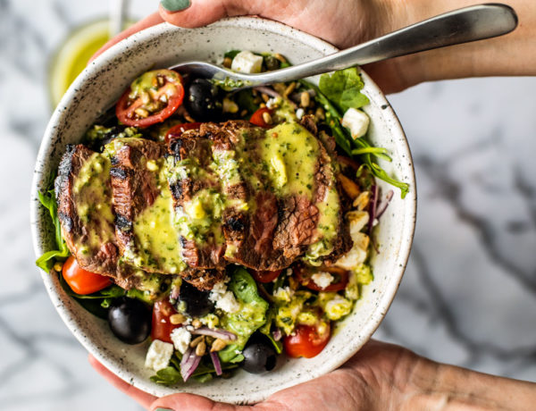 Hands holding up a bowl of Greek Steak Salad drizzled with herb and garlic vinaigrette.