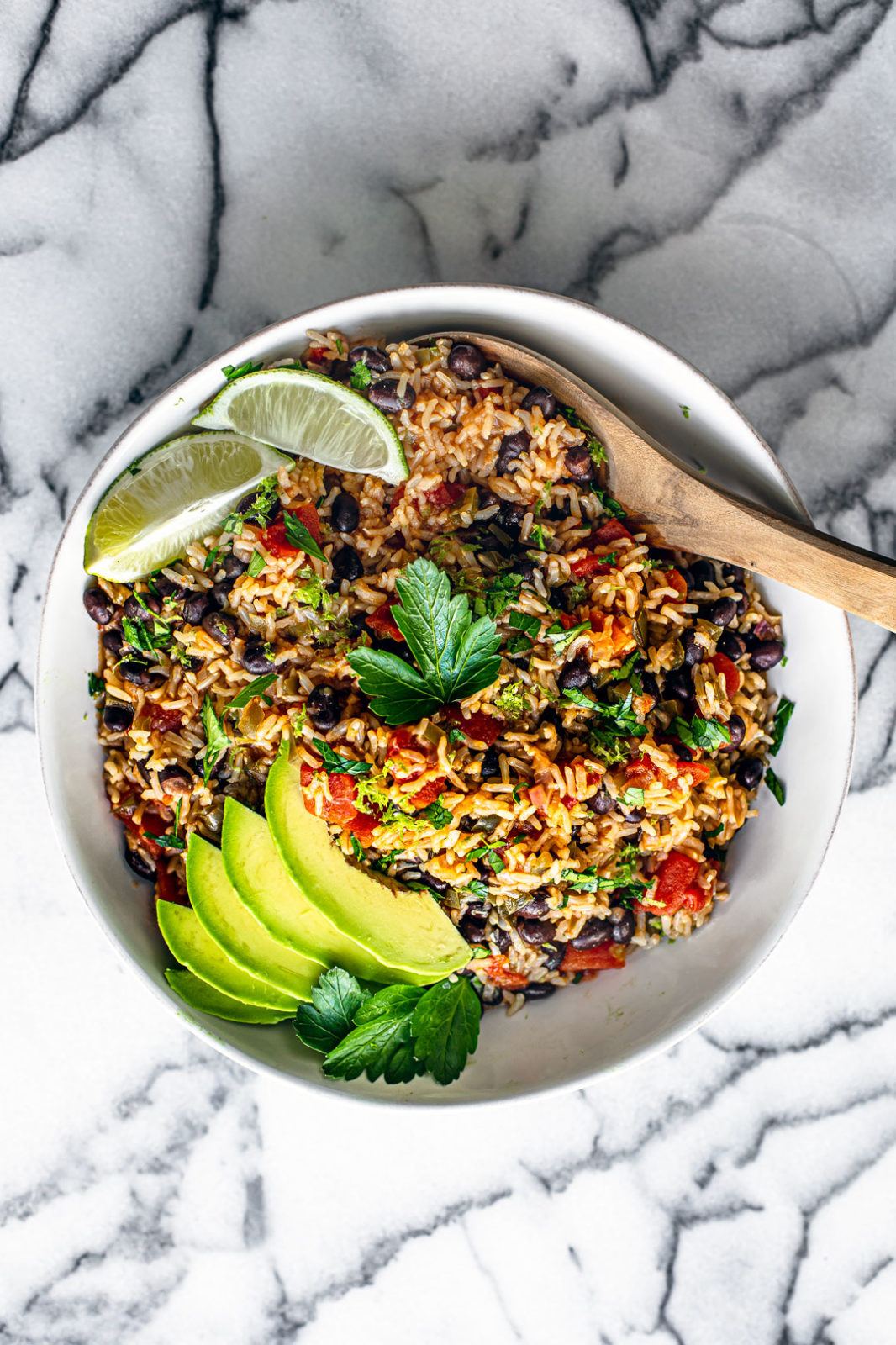 Aerial shot of serving bowl full of Instant Pot Mexican Rice garnished with fresh parsley, sliced avocado, and lime wedges.