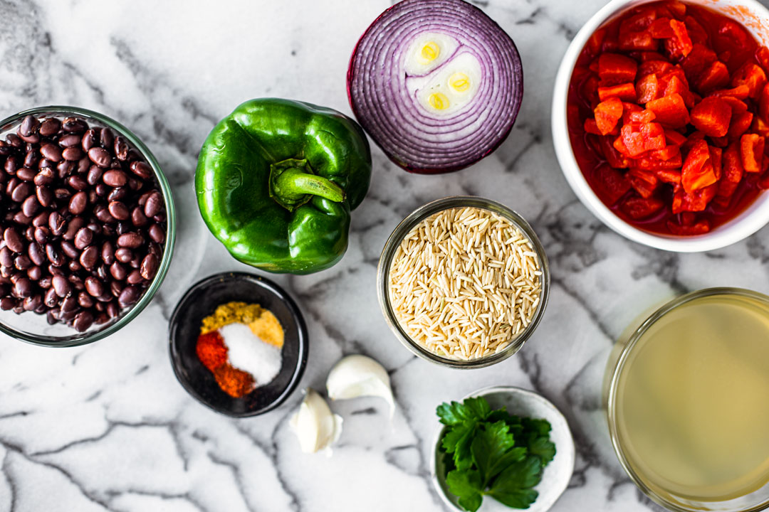 Ingredient bowls and fresh produce laid out over a marble background, including green bell pepper, rice, spices, fresh herbs, black beans, and tomatoes.