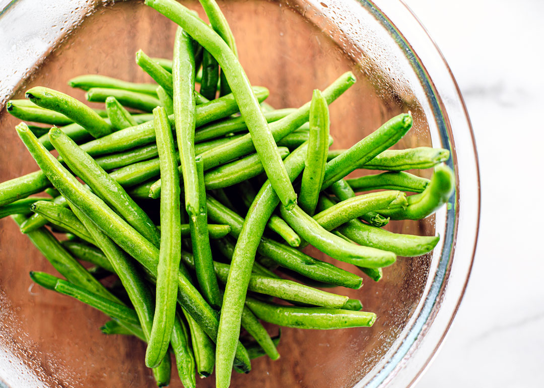 Glass bowl full of fresh green beans.