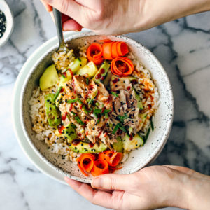 Hands holding a big bowl of rice, mackerel, cucumber, avocado, and carrots.