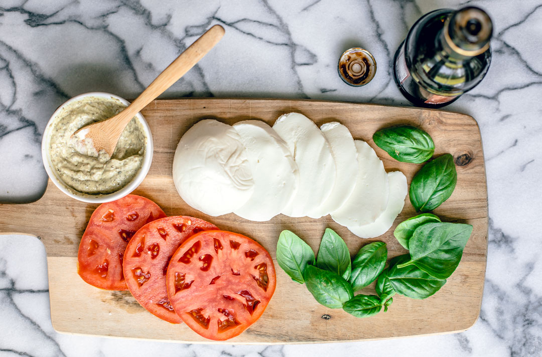 Wooden board topped with fresh basil, mozzarella, tomatoes, and a serving bowl of pesto mayo.