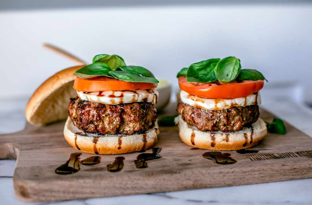 Two Summer Caprese Burgers on a wooden serving board.