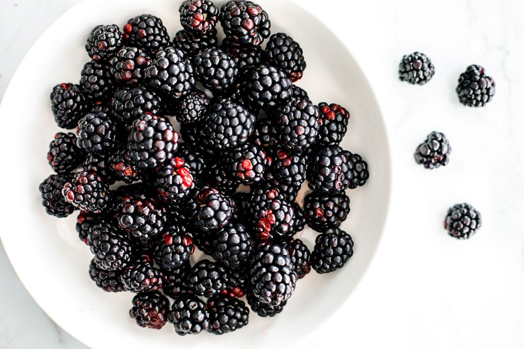 Big white bowl of blackberries.