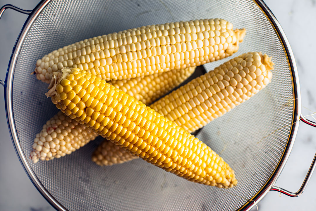 Fresh cobs of corn in a strainer.