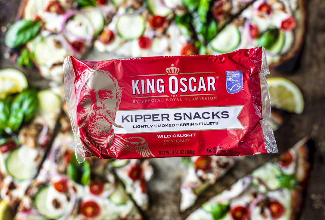 Close up of package of King Oscar Kipper Snacks with summer flatbread in the background.