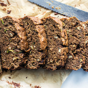 Zucchini bread slices lined up with a bread knife.