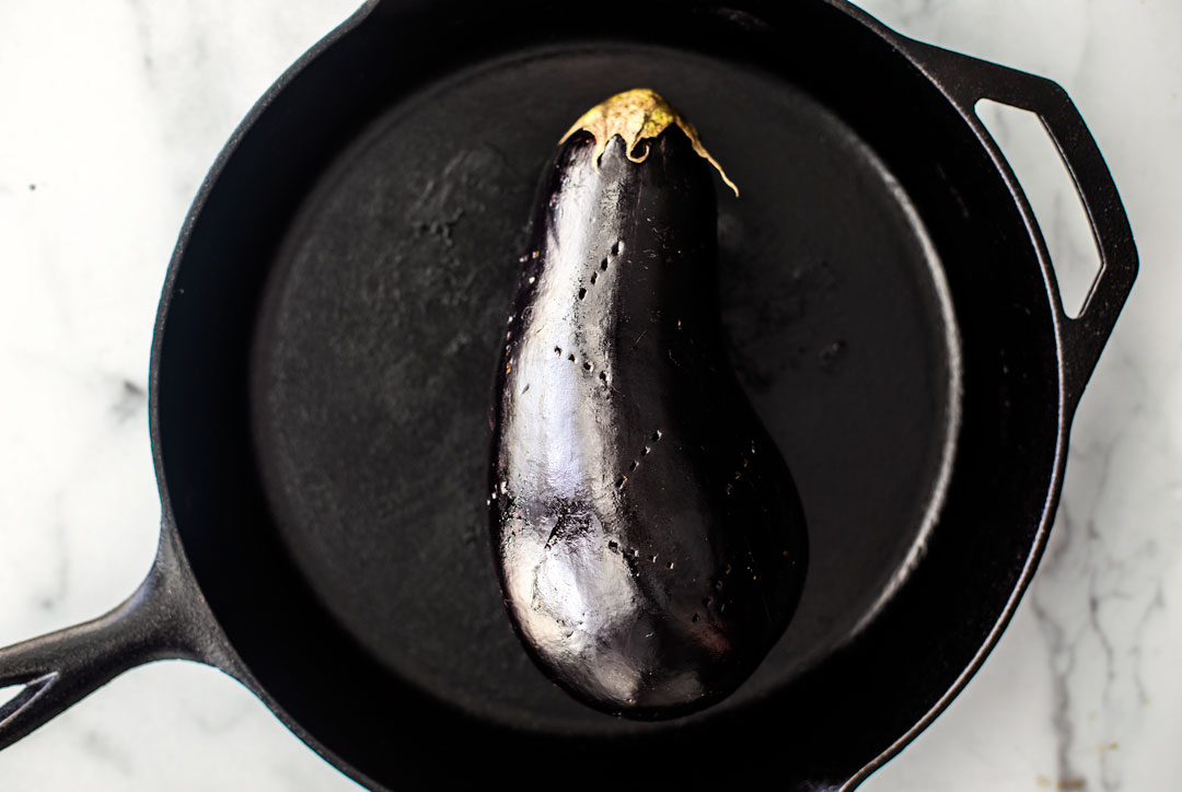 Pierced eggplant in a cast iron skillet.