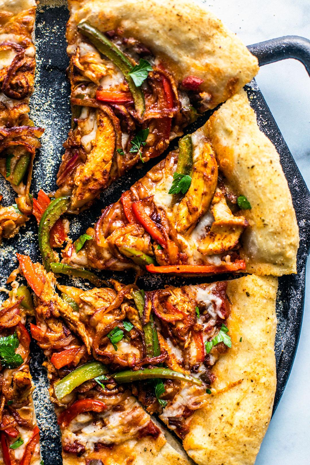 Chicken Fajita Pizza slices on a cast iron pizza pan.
