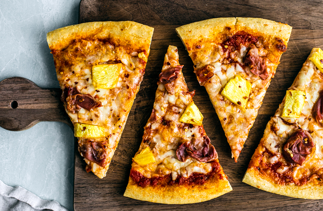 Triangular slices of pizza on a cutting board.