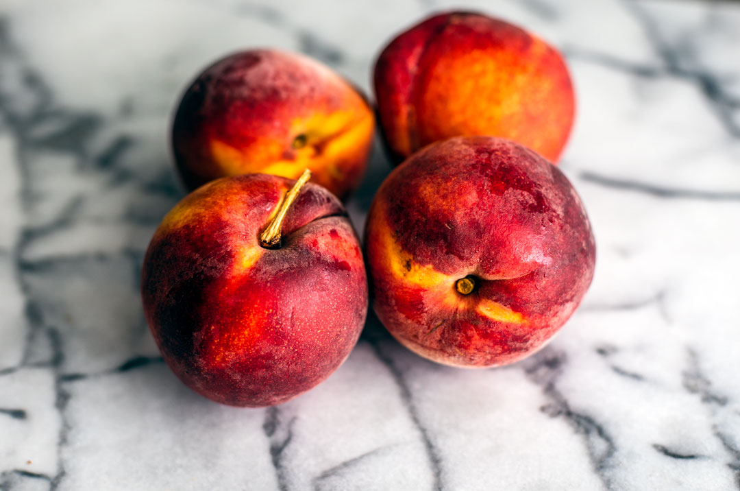 Peaches on marble countertop.