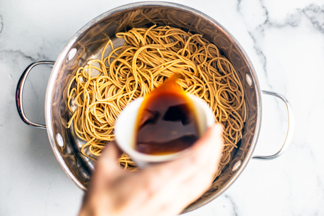 Sesame ginger sauce being drizzled over cooked soda noodles in a pot.