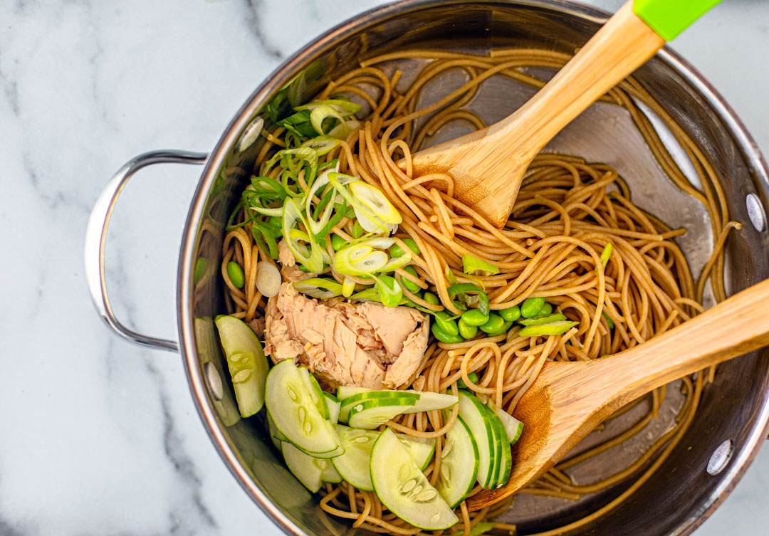 Soba noodles in a pot tossed with edamame, cucumbers, and salmon flakes.