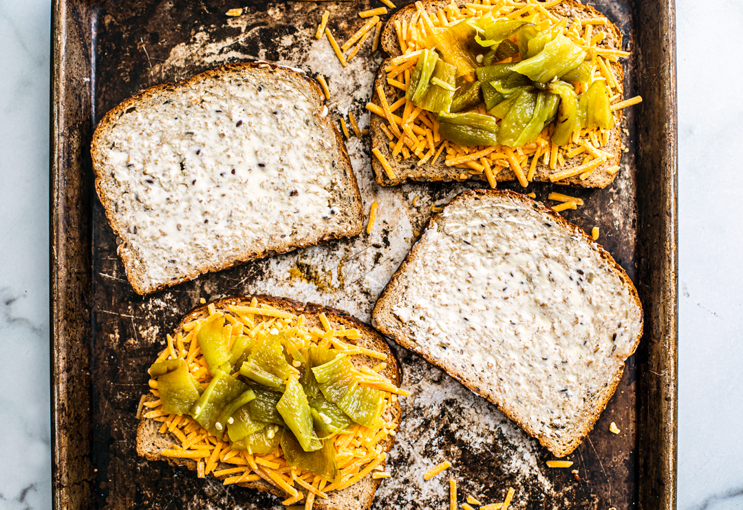 Two slices of buttered bread on a baking sheet along with two slices of bread topped with cheddar cheese and roasted Hatch chiles.