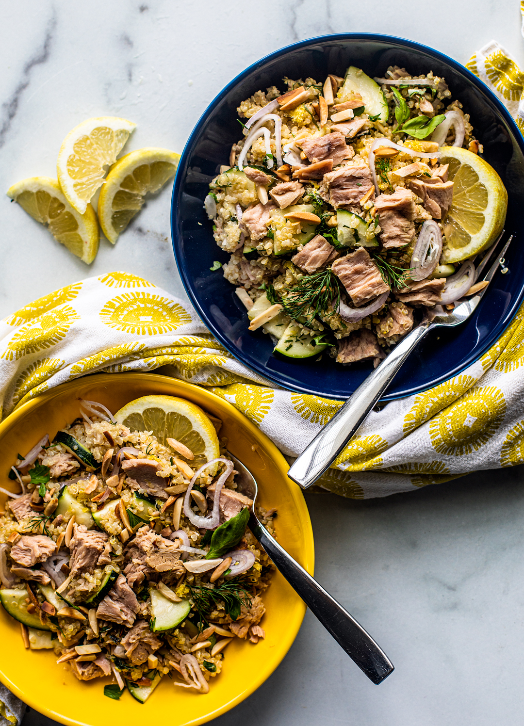 Two bowls of quinoa topped with large flakes of tuna and lemon wedges.