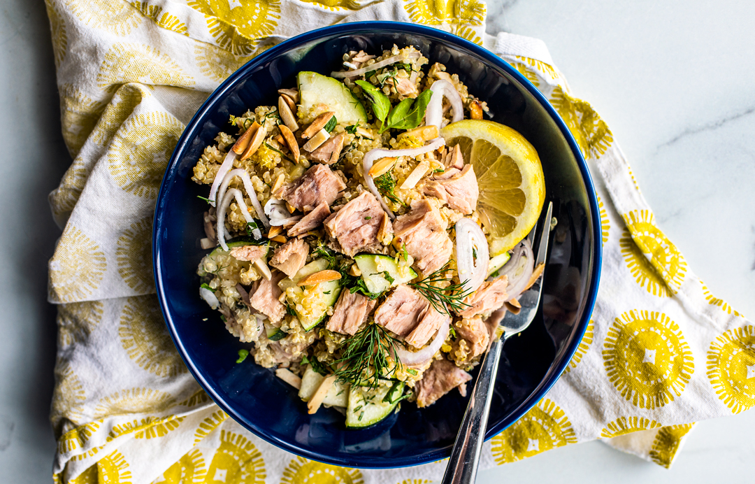Bowl of quinoa salad topped with tuna and lemon wedges.