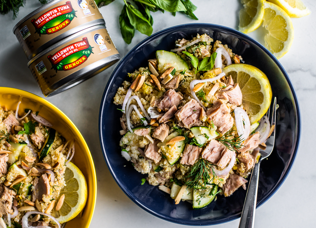 Bowls of quinoa salad with cans of Genova tuna stacked next to them.