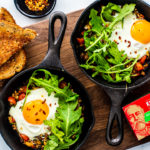 Two miniature skillets filled with Fisherman's Eggs and topped with arugula.