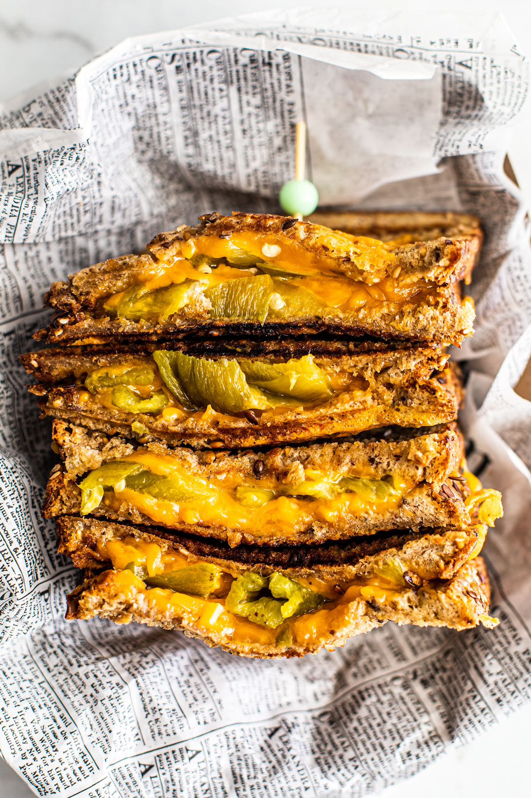 Vertical shot of cut halves of hatch chile grilled cheese stacked on top of one another.