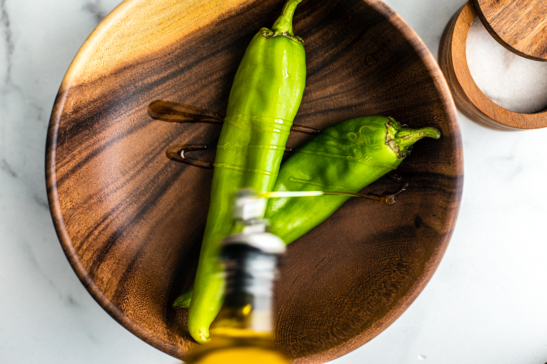 Two Hatch chiles in a bamboo bowl being drizzled with olive oil.