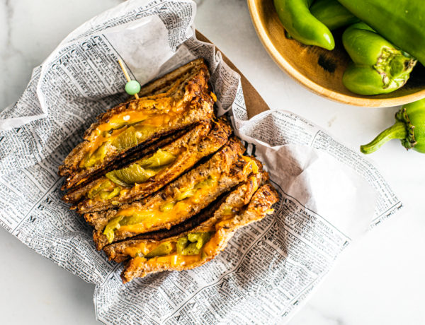 Hatch chile grilled cheese in newspaper next to a bowl of fresh Hatch chiles.